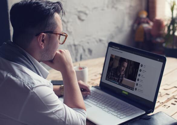 Pessoa estudando inglês pelo computador em um laptop sentado à mesa