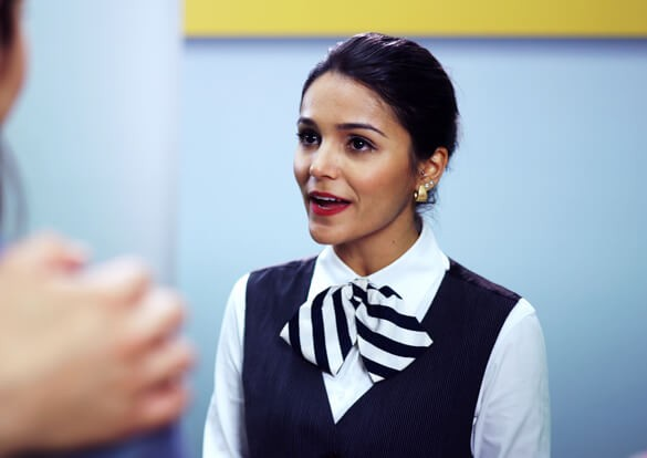 Comissária de bordo conversando com passageiros