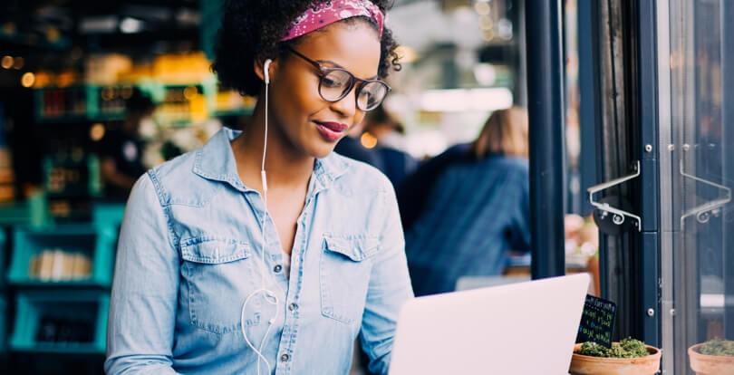 Mulher jovem estudando inglês em café no laptop